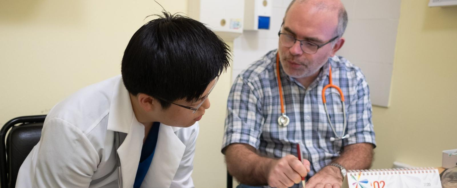 A student doing a medical internship in Argentina consults with a local doctor.